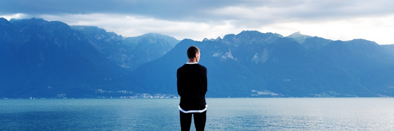 man standing in front of lake and mountains