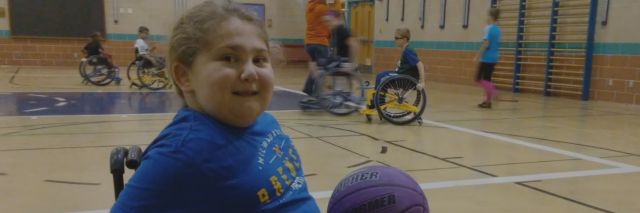 little girl in wheelchair playing basketball