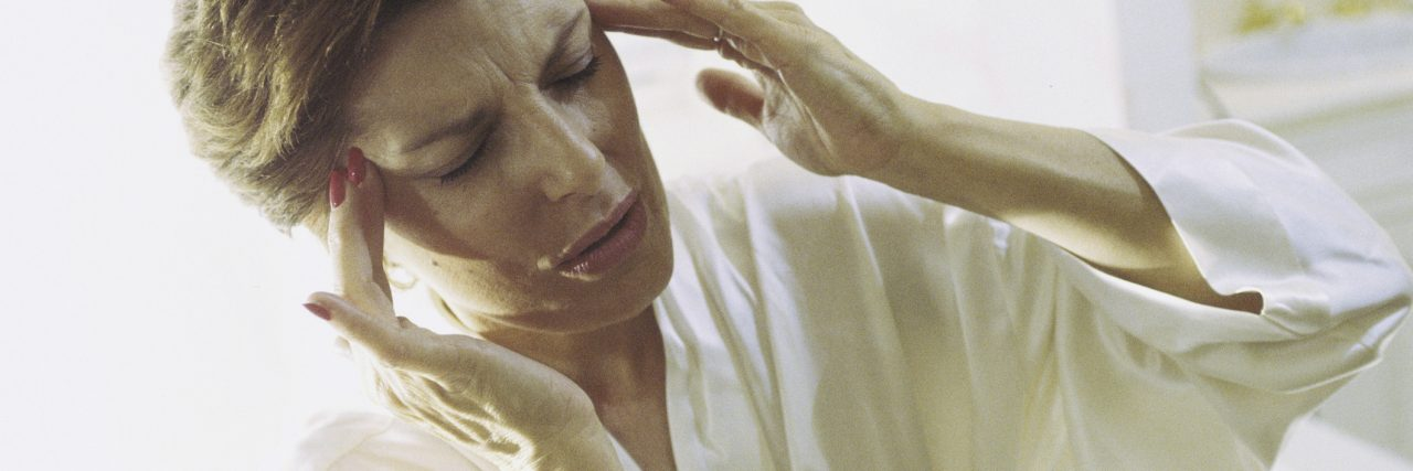 Woman holding the side of her head in pain