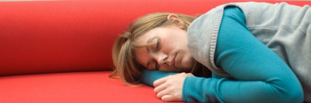 woman sleeping on a red couch