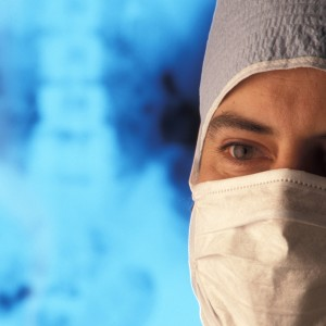 dotor with a surgical mask standing in front of x ray