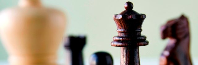 Wooden chess pieces on chess board