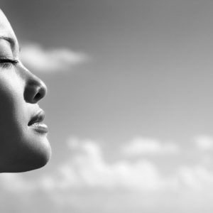 Black and white photo of profile of woman's face with eyes closed, cloudy sky background