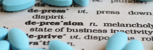 """A close up image of the word """"Depression"""" surrounded by pills."""