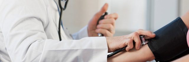 Doctor checking patient's blood pressure.