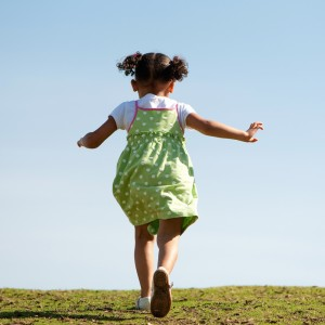 Child running up grassy hill with blue sky in the background