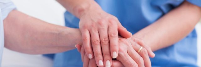 Close up of a nurse touching hand of a patient
