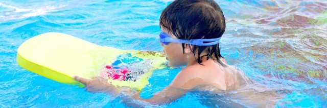 Boy learning to swim in swimming pool, wearing goggles and holding a kickboard