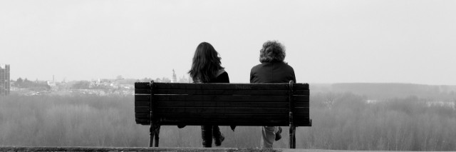 Two people sitting on bench in black and white
