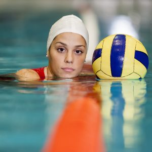Young woman playing water polo in the pool