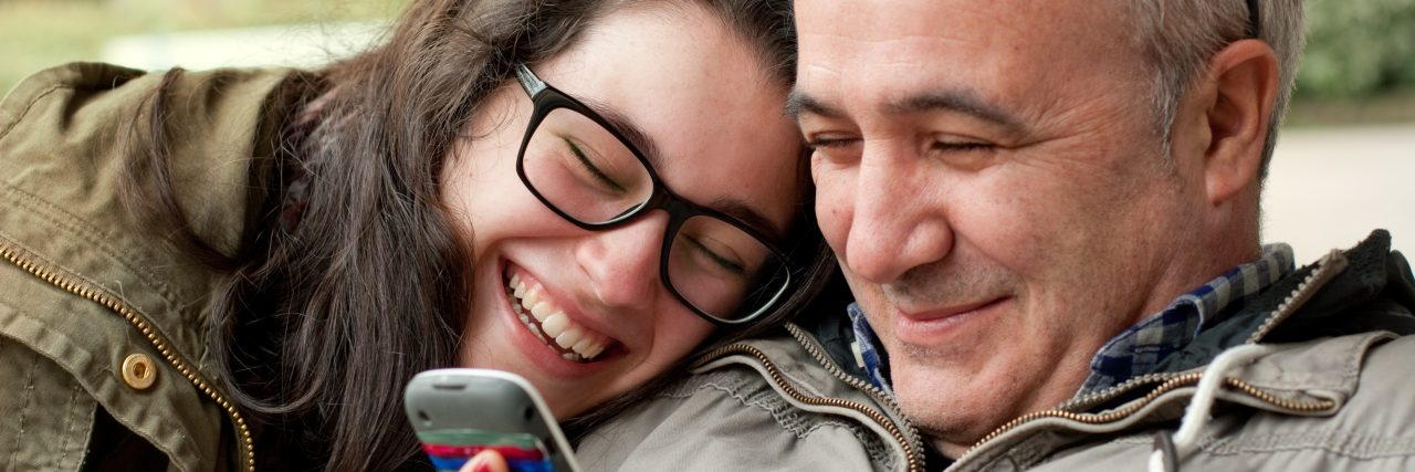 Father and teenage daughter with head in his shoulder sharing something funny in a mobile phone