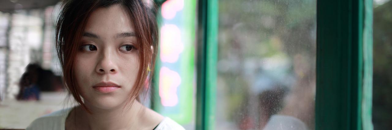 sad woman asian ethnicity sitting by window