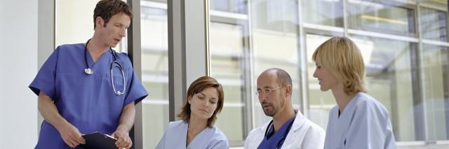 Doctors and nurses talking by window in hospital