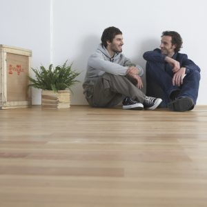 Men sitting on wooden floor, smiling