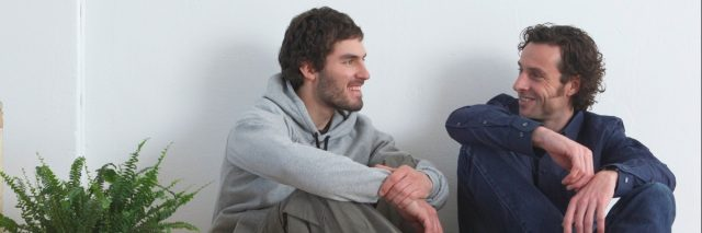 Men sitting on wooden floor, smiling