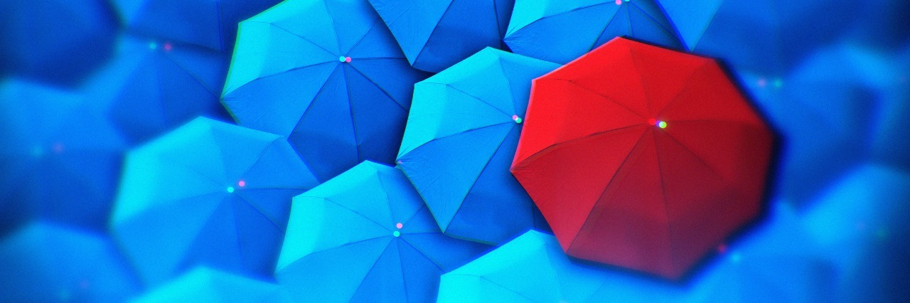 blue umbrellas with one red umbrella