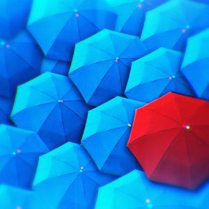 blue umbrellas with one red umbrella