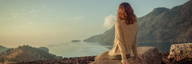 woman sitting on a rock overlooking a lake and mountains at sunrise