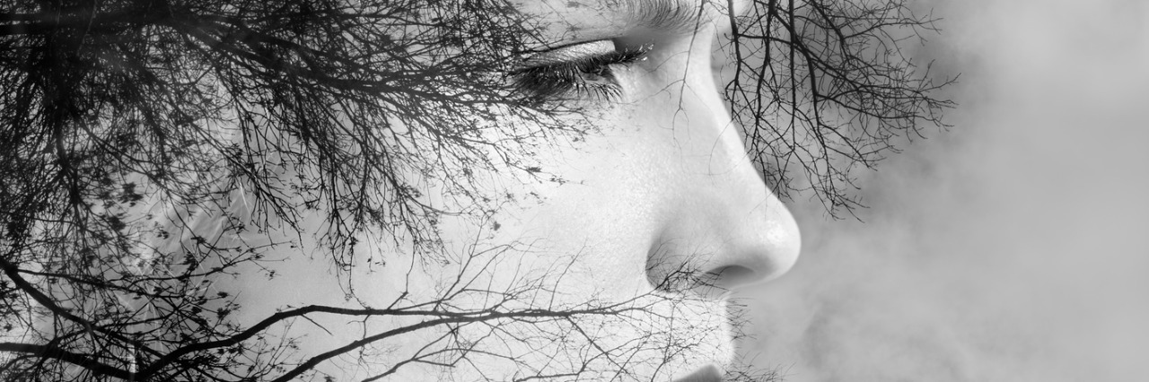 creative portrait of beautiful young woman made from double exposure effect using photo of trees and nature, black and white toned
