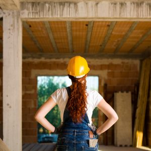 female bricklayer with her hands on her hips looks at house under construction