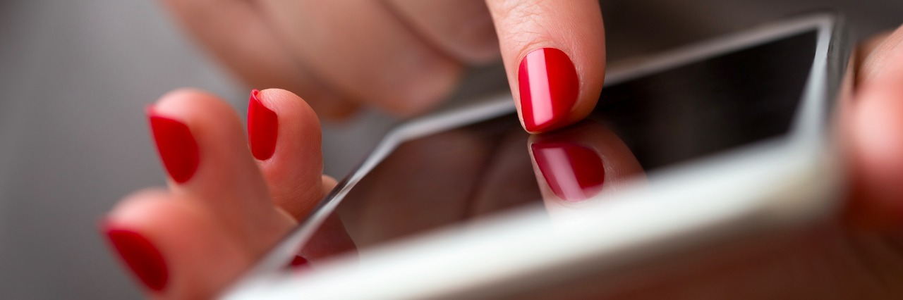 Closeup of a woman hand using smart phone, focus on finger with red nail polish typing on the screen , shallow depth of field.