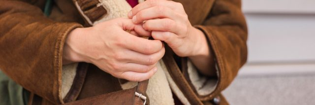 guarded woman picking nails wearing heavy coat