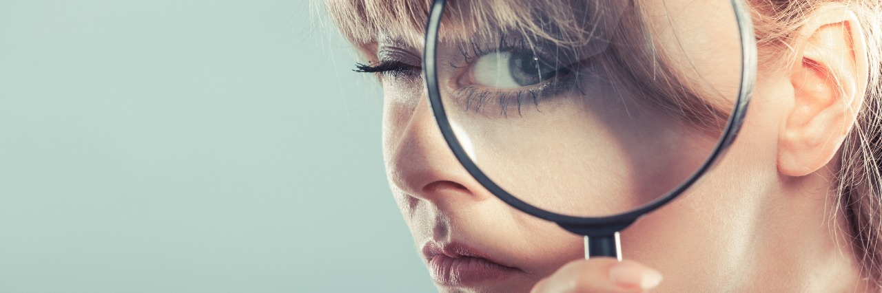 woman looking through magnifying lens with her eye appearing large