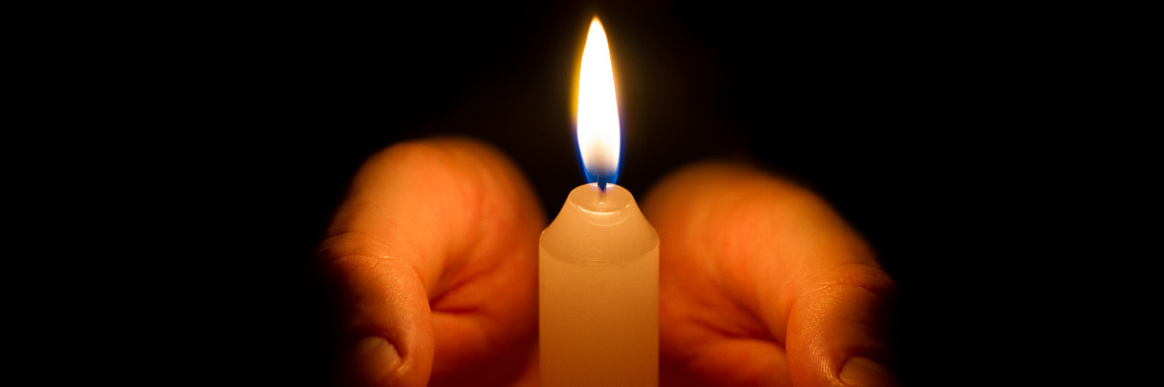 Hands holding a lit candle in the darkness.