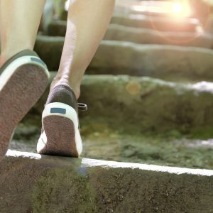 feet walking up stairs towards sun