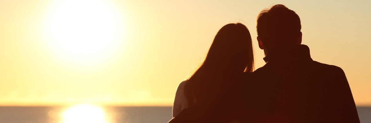 silhouette of woman and man sitting on a bench in front of the ocean watching the sunset