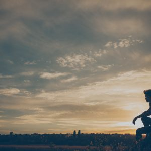 Silhouette of young man sitting on sunset or sunrise. Confident teenage boy thinking on cliff stone.