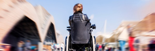 Woman in a wheelchair outdoors.