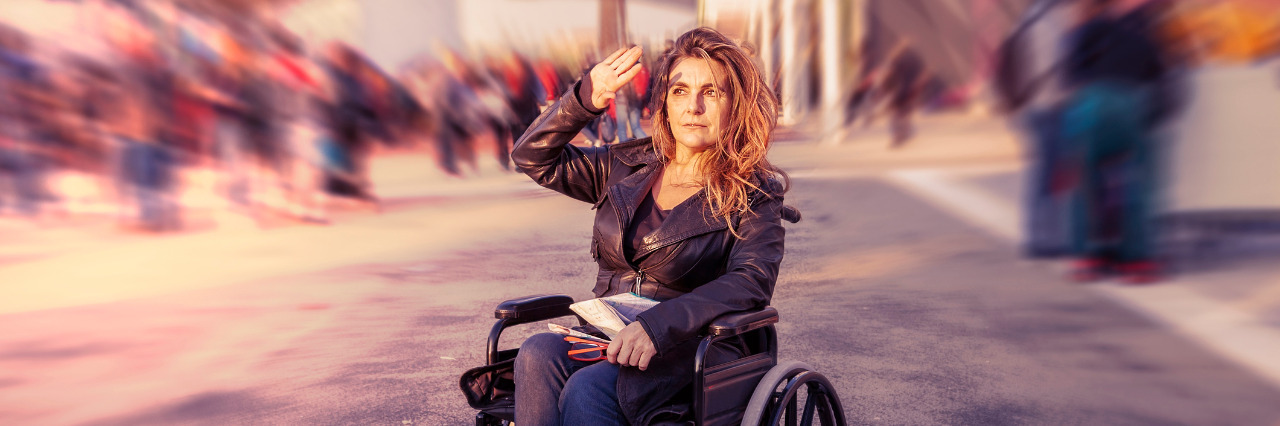 Woman in a wheelchair outdoors, artistic image with blurred crowds moving past in background.