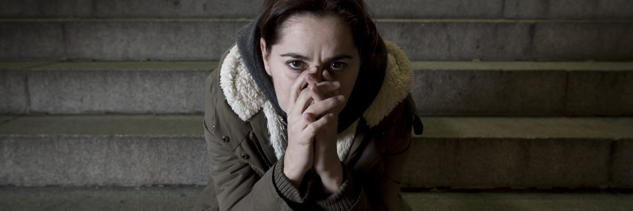 sad woman alone on street subway staircase