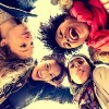 Group of young women hugging in a circle - Four students smiling at camera - Best friends spending time together