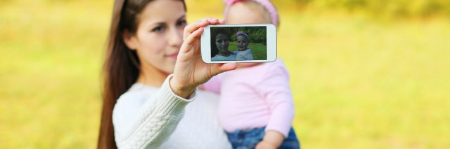 Mother and baby taking self-portrait on smartphone in sunny summer