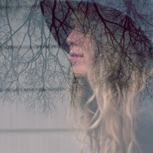 An in camera double exposure of a woman with long hair wearing a fedora hat and upside down trees.