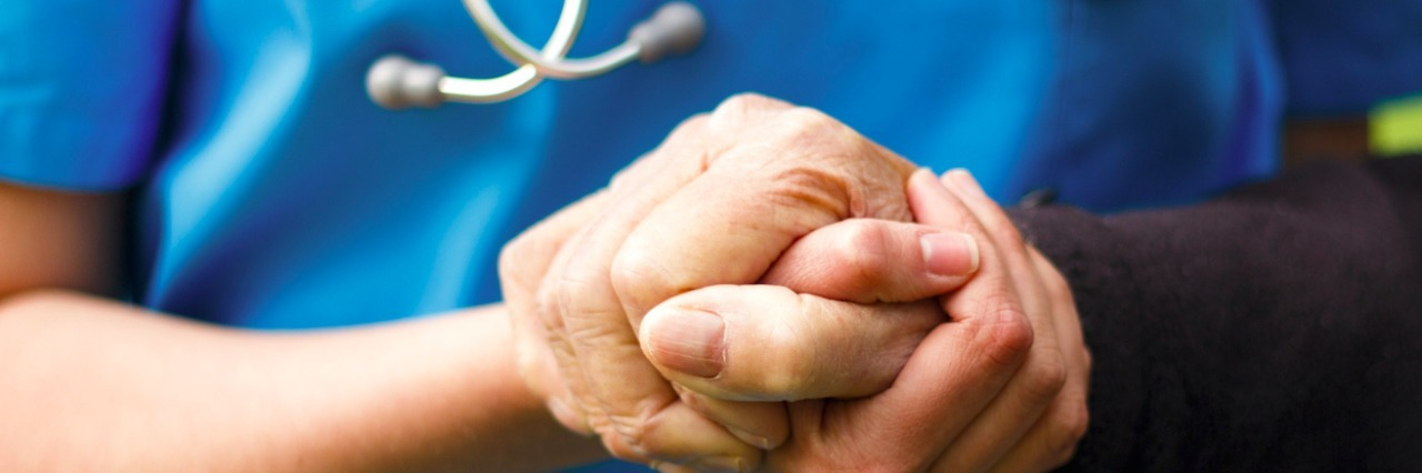 Medical professional holding hand of patient