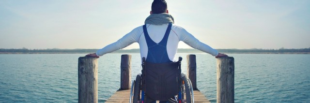 disabled Young man in wheelchair on a boardwalk on lake enjoying the view