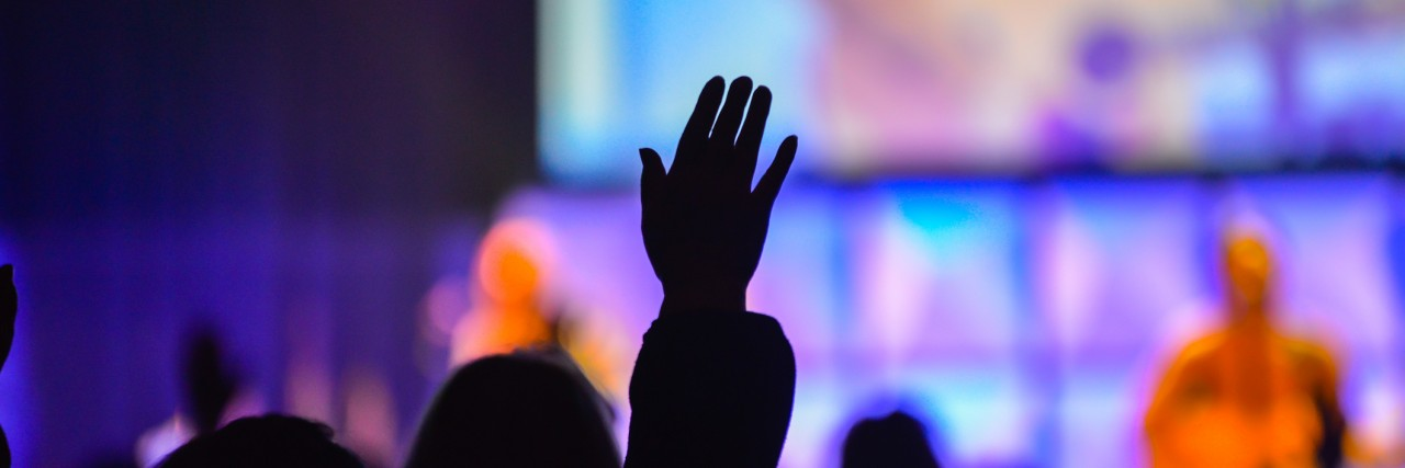 Worshipers holding their hands in the air at a Christian worship service