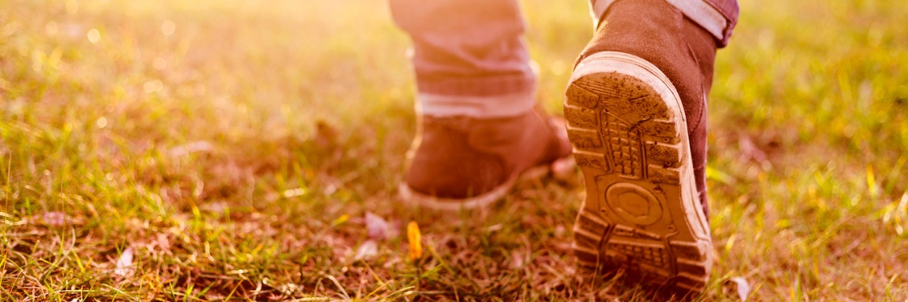 Close-up of person's legs and shoes walking on muddy grass