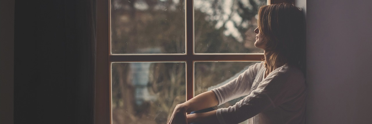 woman sitting in a windowsill looking out at a cloudy sky