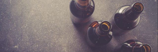 close up of beer bottles on a dark table