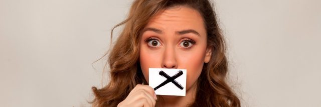shocked young girl with X sign drawn on paper over her mouth