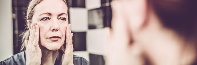 woman looking at herself in the mirror with her hands on her cheeks