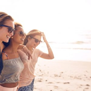 Group of happy young women walking on a beach.
