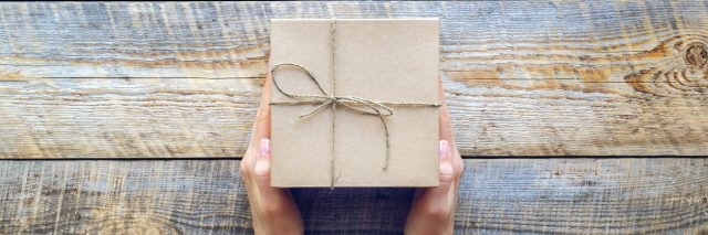 Womans hand holding craft gift box on wooden table close up