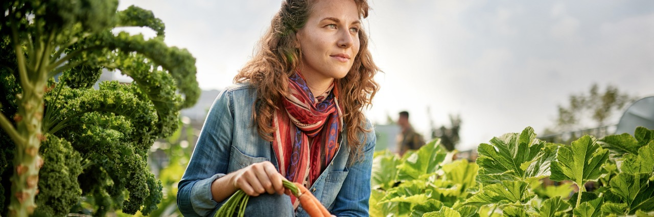 woman holding carrots and working in her garden