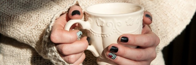 woman wearing a sweater and holding a white mug with painted fingernails