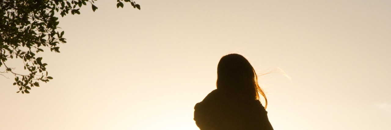 Silhouette of woman standing near tree at sunset
